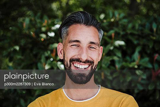 portrait of handsome smiling man using in city, Madrid, Spain - p300m2287309 von Eva Blanco