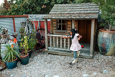 Young black girl with long braids jumping from wooden playhouse - p1166m2136996 by Cavan Images