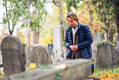 Mourning young man kneeling in front of a grave on a cemetery - p1166m2146385 by Cavan Images