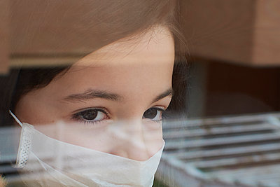 Girl with face mask looking out the window quarantined by coronavirus - p1166m2189788 by Cavan Images
