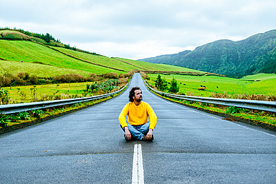 Azores, Sao Miguel, Man sitting on an empty road - p300m1568136 von Kiko Jimenez