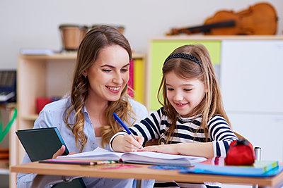 Smiling teacher with schoolgirl in class - p300m1588126 by gpointstudio