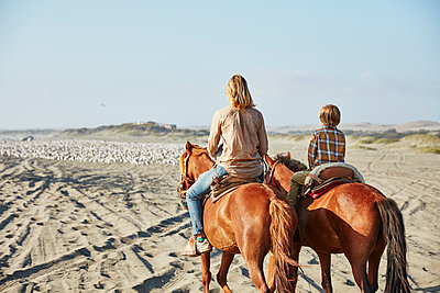 Chile, Vina del Mar, mother with son riding horses on the beach - p300m2069195 by Stefan Schütz