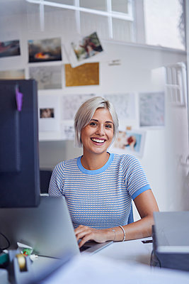 Young woman working in office, sitting at desk, smiling - p300m2081086 by Philipp Nemenz