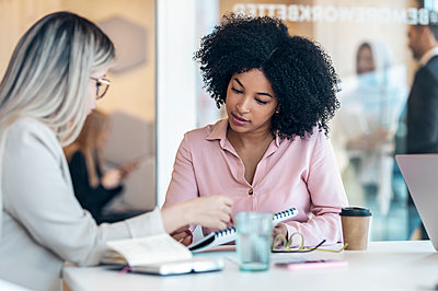 Businesswomen discussing at desk in office - p300m2282118 by Josep Suria