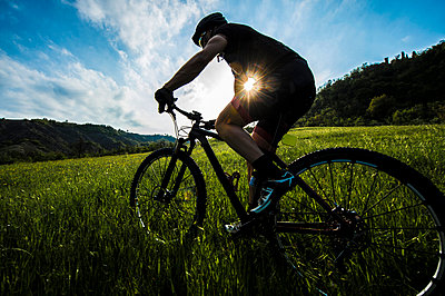 Man riding mountain bike in nature in the Bologna countryside, Italy - p307m937561f by Maurizio Borsari