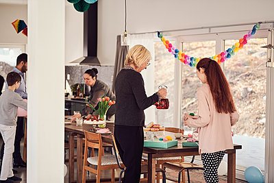 Multi-generation family arranging food and drink on table during birthday party - p426m1580234 by Maskot