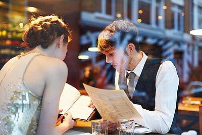 Couple reading menu in restaurant - p429m1022843 by Liam Norris