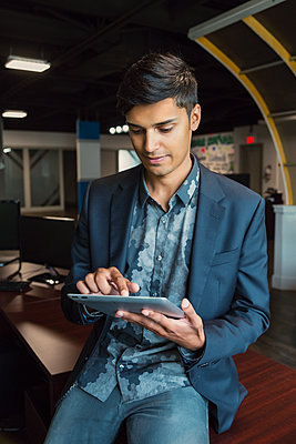 Young millennial businessman using his technology in the workplace; Sherwood Park, Alberta, Canada - p442m1580577 by LJM Photo