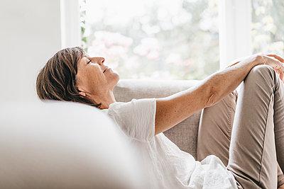 Reife Frau entspannt auf dem Sofa - p586m1178463 von Kniel Synnatzschke
