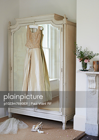 Wedding gown hanging from wardrobe