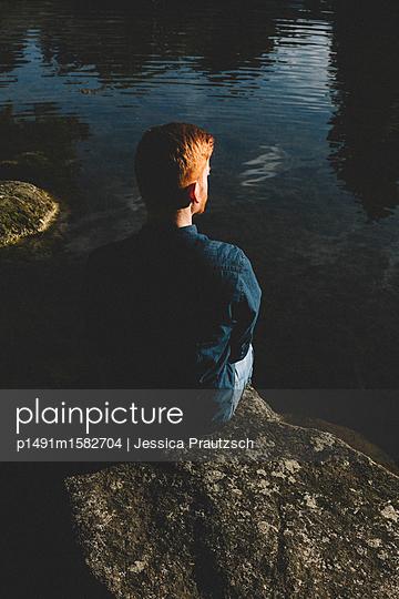 Junger Mann sitzt am Wasser und schaut in die Ferne - p1491m1582704 von Jessica Prautzsch