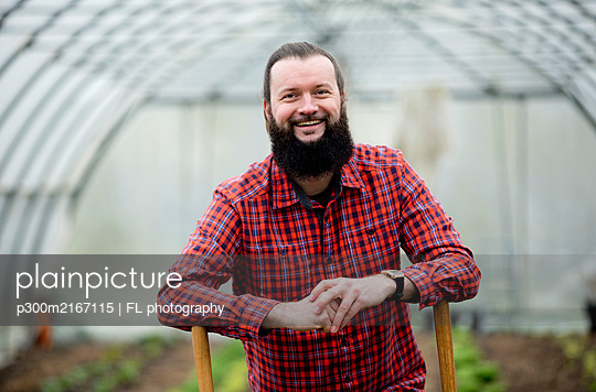 Portrait of happy man, working in greenhouse - p300m2167115 by FL photography