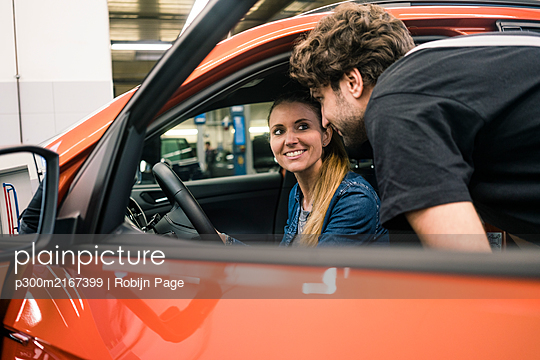 Car mechanic talking to client in car - p300m2167399 by Robijn Page