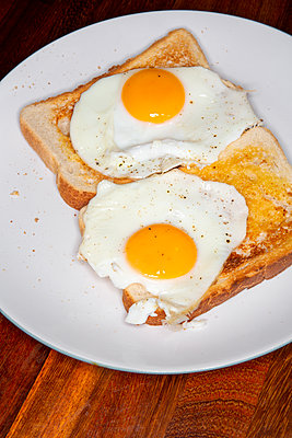 Two freshly cooked fried eggs from a griddle on fresh buttered toast on white plate. - p1057m2164230 by Stephen Shepherd