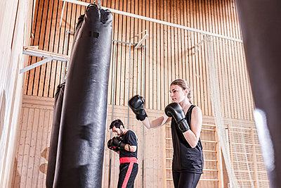 Coach and female boxer practising at punchbag in sports hall - p300m2144491 von Stefanie Baum