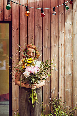 Smiling mid adult woman holding flowers while standing against tiny house - p300m2214034 by Maya Claussen