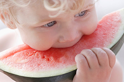 Boy eating watermelon - p300m700726f by Tom Chance