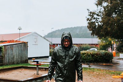 Man walking in rainy weather - p312m2239699 by Jennifer Nilsson