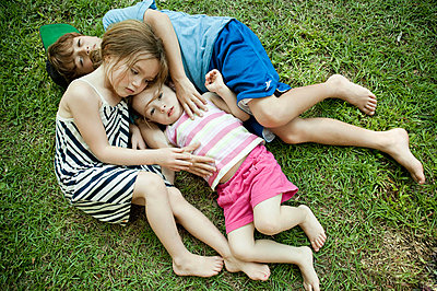 Children laying in grass together - p429m768182 by Robyn Breen Shinn