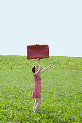 Woman in red red with red suitcase - p4541282 by Lubitz + Dorner