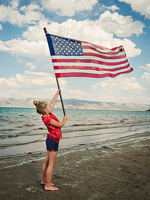 Caucasian girl holding American flag at beach - p555m1303262 by Erik Isakson