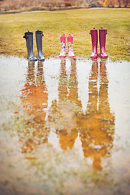 Reflection of people from rain boots in puddle - p555m1409684 by Shestock