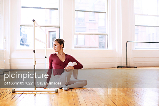 Young ballet dancer sitting in studio