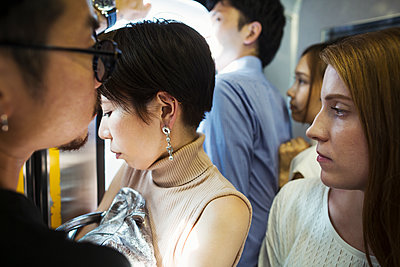 Small group of people standing on a subway train, Tokyo commuters.  - p1100m1531113 by Mint Images