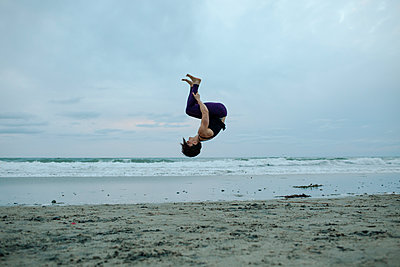 Carefree woman backflipping at beach while exercising against sky - p1166m1507978 by Cavan Images