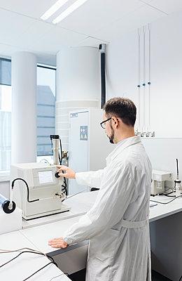 Scientist working in laboratory adjusting a device - p300m2160403 by Hernandez and Sorokina