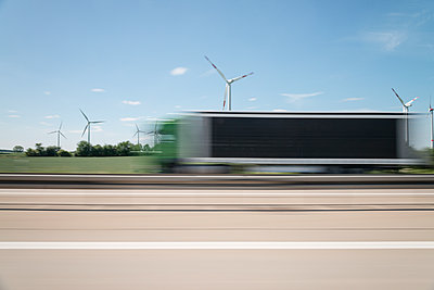 Wind farm along the highway blurred view - p335m1152373 by Andreas Körner