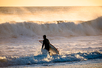 Surfer walking in sea at sunset - p343m1585190 by Cate Brown