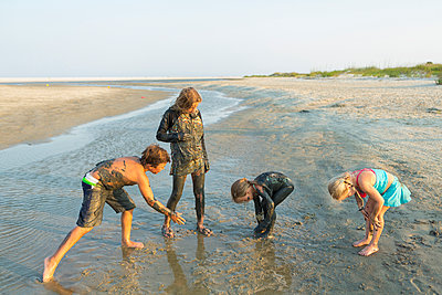 Caucasian brother and sisters covered in mud playing on beach - p555m1522776 by Marc Romanelli