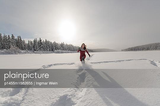 Junge Frau rennt durch den Schnee  - p1455m1582655 von Ingmar Wein