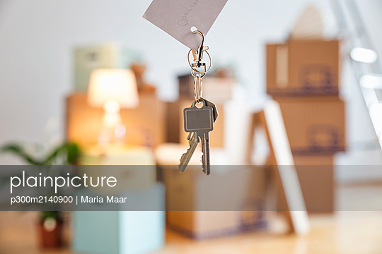 House key in front of cardboard boxes in an empty room in a new home - p300m2140900 by Maria Maar