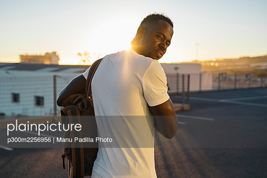Man with backpack at parking lot during sunset - p300m2256956 by Manu Padilla Photo