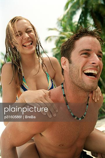 young couple enjoying a piggyback ride on a tropical beach