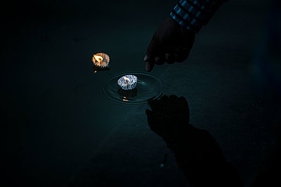 Hand pushing a candle in water - p1007m1144317 by Tilby Vattard