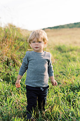 Young boy playing in a field. - p1166m2151873 by Cavan Images