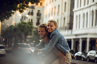 Happy young man carrying girlfriend piggyback in the city - p300m2155576 by Maya Claussen