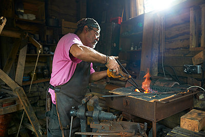 Blacksmith working in his forge - p429m2023186 by Peter Muller
