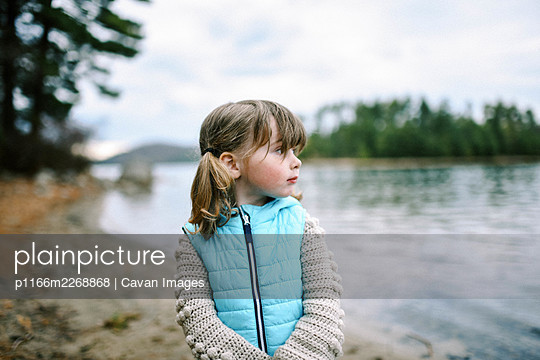 Little toddler girl with pigtails at shore looking out to the lake - p1166m2268868 by Cavan Images