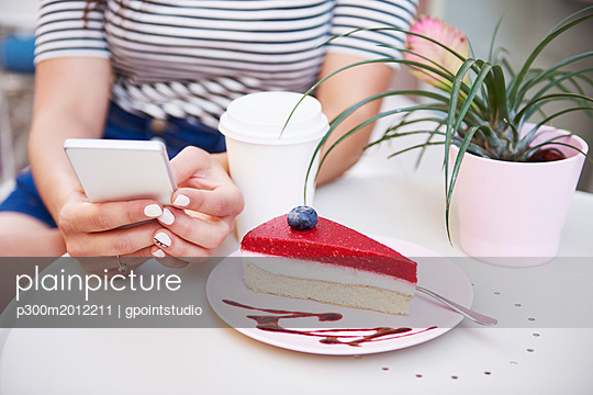 Close-up of woman using cell phone and eating cake at an cafe - p300m2012211 von gpointstudio