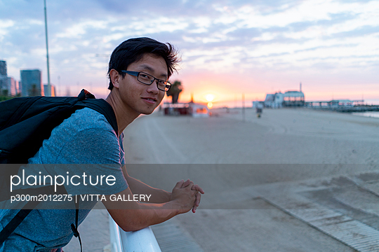 Young Chinese man with backpack looking at beach - p300m2012275 von VITTA GALLERY