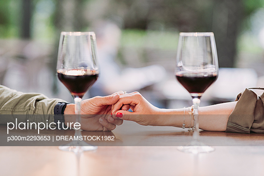 Man holding hand of girlfriend on bar table - p300m2293653 by DREAMSTOCK1982