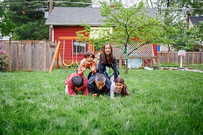 A smiling family are stacked up in human pyramid in backyard play - p1166m2157362 by Cavan Images