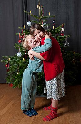 Geschwister vor Weihnachtsbaum - p1311m1203516 von Stefanie Lange