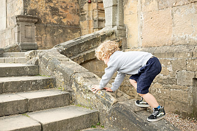 Blond boy climbs on stone wall - p1520m2099021 by Michael Leckie