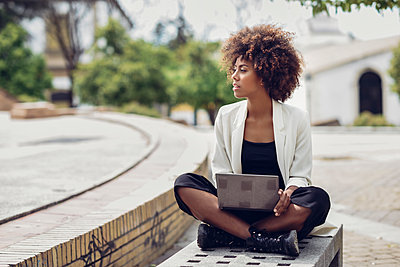 Fashionable young woman with curly hair sitting on bench with laptop - p300m2005557 von Javier Sánchez Mingorance